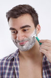 Happy young man shaving Royalty Free Stock Images