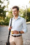 Happy young man in shirt carrying bag walking. At the city park with cup of coffee Stock Image