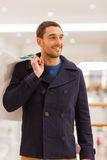 Happy young man with shopping bags in mall Stock Images