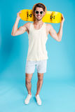 Happy young man in shorts, hat and sunglasses with skateboard Royalty Free Stock Photos