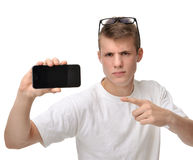 Happy young man show display of mobile cell phone with blank scr. Happy young man show display of mobile cell phone pointing finger at blank screen isolated on a Stock Photos
