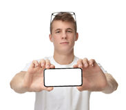 Happy young man show display of mobile cell phone with blank scr. Een and smiling isolated on a white background. Focus on hand with mobile phone Royalty Free Stock Image