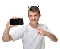 Happy young man show display of mobile cell phone with blank scr. Een and smiling isolated on a white background. Focus on hand with mobile phone Stock Photo