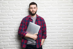 Happy young man show laptop in hands against brick wall Royalty Free Stock Photos
