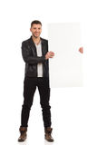 Happy young man showing the blank banner. Stock Photos