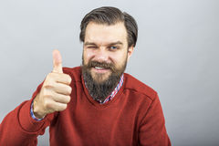 Happy young man showing OK sign with his thumb up and blinking. Over gray background royalty free stock images