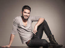 Happy young man sits on the floor and smiles Stock Photos