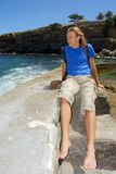 Happy young man sits on stone Royalty Free Stock Photo