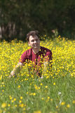 Happy young man sits among yellow flowers Royalty Free Stock Photo