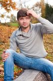 Happy young man sitting in autumn park Stock Photos