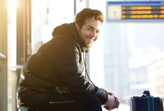 Happy young man sitting with bag at train station Royalty Free Stock Image