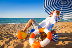Happy young man sitting on the beach Stock Image