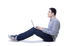 Happy young man sitting on floor with laptop Stock Photo