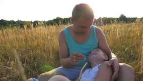 Happy young man sitting on grass at the field and playing with his baby boy. Cheerful daddy and his child having fun. Together in nature. Father tickling his stock video
