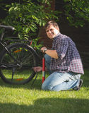 Happy young man sitting on grass and park and pumping up tires. Portrait of happy young man sitting on grass and park and pumping up tires Stock Photo