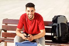 Happy young man sitting with luggage and listening to music with mobile phone. Portrait of happy young man sitting with luggage and listening to music with Stock Image