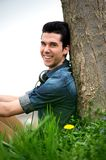 Happy young man sitting in nature Royalty Free Stock Images