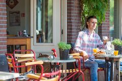 Happy young man sitting in outdoors cafe at Stock Photo