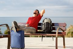 Happy young man sitting outside with luggage and listening to music with mobile phone and earphones. Portrait of happy young man sitting outside with luggage and Royalty Free Stock Image