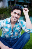 Happy young man sitting in a park Stock Photos