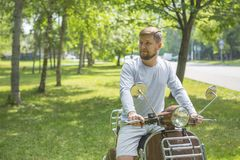 Happy young man sitting on scooter royalty free stock images