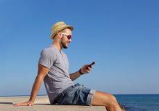 Happy young man sitting by the sea with mobile phone Stock Photo