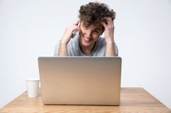 Happy young man sitting at the table with laptop Stock Photos