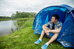 Happy young man sitting in tent at camping. Travel, tourism, hike, equipment and people concept - happy young man sitting in tent at camping on lake or river stock images