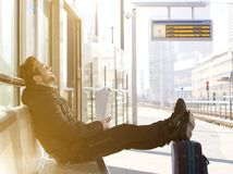 Happy young man sitting with travel bag at the train station Stock Image