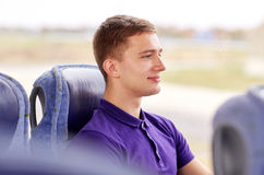 Happy young man sitting in travel bus or train. Transport, tourism, road trip and people concept - happy young man sitting in travel bus or train and looking Stock Images
