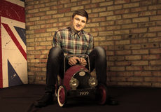 Happy Young Man Sitting on Vintage Toy Car Royalty Free Stock Photos