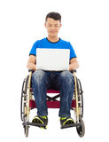 Happy young man sitting on a wheelchair with a laptop Stock Image