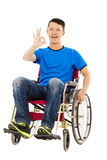 Happy young man sitting on a wheelchair and ok gesture Royalty Free Stock Photography