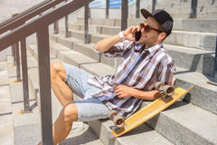 Happy young man with skate using smartphone. Cheerful male skater is talking on mobile phone and laughing. He is sitting on stairs outdoors and relaxing Royalty Free Stock Images