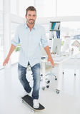 Happy young man skateboarding in creative office Stock Image