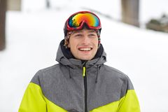 Happy young man in ski goggles outdoors. Winter, leisure, sport and people concept - happy young man in ski goggles outdoors Royalty Free Stock Image