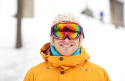Happy young man in ski goggles outdoors. Winter, leisure, sport and people concept - happy young man in ski goggles outdoors Stock Image