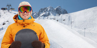 Happy young man in ski goggles over mountains Royalty Free Stock Images