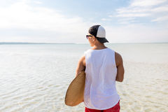 Happy young man with skimboard on summer beach Stock Photo