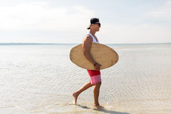 Happy young man with skimboard on summer beach Stock Photos