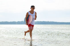 Happy young man with skimboard on summer beach Royalty Free Stock Photography
