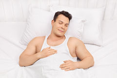 Happy young man sleeping on a bed Royalty Free Stock Images
