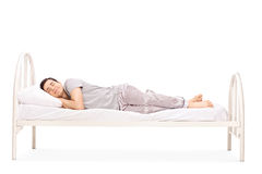 Happy young man sleeping in a bed. Isolated on white background royalty free stock photos