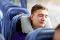 Happy young man sleeping in travel bus with pillow. Transport, tourism, road trip and people concept - happy young man sleeping in travel bus with pillow Royalty Free Stock Image