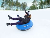 Happy young man sliding down on snow tube Royalty Free Stock Images