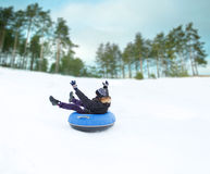 Happy young man sliding down on snow tube Stock Photos