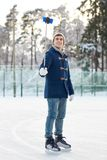Happy young man with smartphone on ice rink Stock Photos