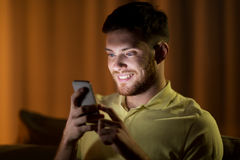 Happy young man with smartphone at night Royalty Free Stock Image