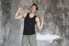 Happy young man smiling. Close-up of a man laughing in front of a rock Royalty Free Stock Photo