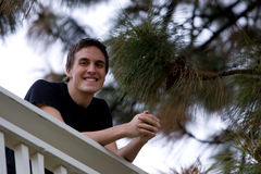 Happy young man smiling. By pine tree Royalty Free Stock Photo